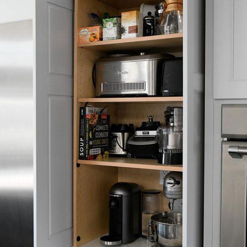 Pocket door appliance cabinet